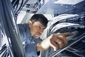 Technician engeneer (30-35) is checking server's wires in data center